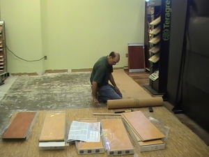"""Here is Earl rolling out 1/8"""" cork underlayment."""